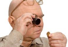 Mãos do magnifier do joalheiro de uma moeda do numismatist Imagem de Stock