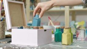 Mãos do manejo o frasco e as garrafas da pintura, escolhendo a cor direita nos vasos vídeos de arquivo