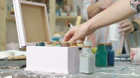 Mãos do manejo o frasco e as garrafas da pintura, escolhendo a cor direita nos vasos filme