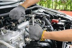 Mãos do mecânico de carro na reparação de automóveis imagens de stock