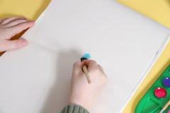 Mãos do menino que pintam na tabuleta Foto de Stock Royalty Free