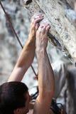 Mãos do montanhista da rocha em um penhasco Fotografia de Stock Royalty Free