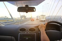 Mãos do motorista da mulher que guardam o painel da direção do carro imagens de stock royalty free
