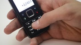 Mãos do número do seletor da pessoa no telefone celular No fundo branco vídeos de arquivo