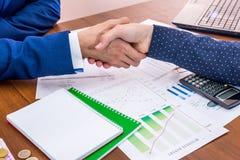 Mãos do negócio que agitam acima do gráfico de negócio Fotografia de Stock Royalty Free