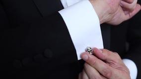 Mãos do noivo do casamento que preparam-se no terno filme