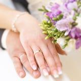 Mãos do noivo e da noiva com alianças de casamento Fotografia de Stock