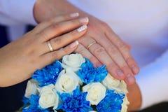 Mãos do noivo e da noiva com alianças de casamento e um weddin Fotografia de Stock