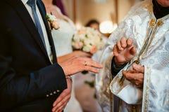Mãos do noivo em uma igreja Fotografia de Stock Royalty Free