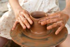 As mãos do oleiro no trabalho