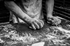 Mãos do padeiro que amassa a massa imagem de stock royalty free