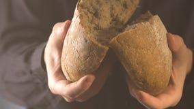 Mãos do padeiro que quebram o pão caseiro Feche acima da vista video estoque