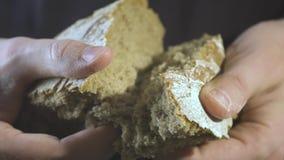 Mãos do padeiro que quebram o pão caseiro Feche acima da vista vídeos de arquivo
