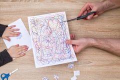 Mãos do pai e do filho que cortam o papel com scisors Imagens de Stock
