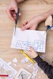 Mãos do pai e do filho que cortam o papel com scisors Fotos de Stock Royalty Free