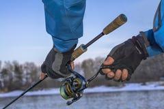 Mãos do pescador com vara de pesca Fotos de Stock