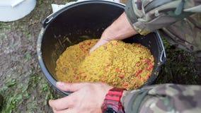 Mãos do pescador que misturam a isca para peixes Processo que cozinha a isca para peixes Pescando a atração filme