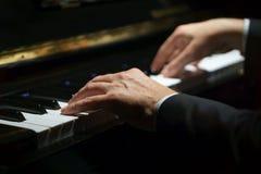 Mãos do pianista do músico profissional em chaves do piano de um piano clássico imagens de stock