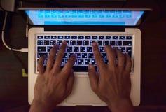 Mãos do programador no teclado iluminado do portátil Vista superior imagem de stock royalty free