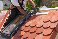 Mãos do roofer que colocam a telha no telhado Instalando a telha vermelha natural Fotografia de Stock Royalty Free