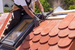 Mãos do roofer que colocam a telha no telhado Instalando a telha vermelha natural Foto de Stock Royalty Free