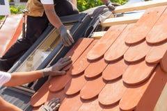 Mãos do roofer que colocam a telha no telhado Instalando a telha vermelha natural Telhado com janelas da mansarda Fotografia de Stock