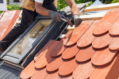 Mãos do roofer que colocam a telha no telhado Instalando a telha vermelha natural usando o martelo Fotografia de Stock