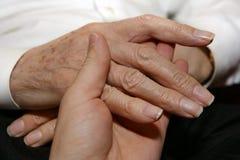 Mãos do sénior da terra arrendada do cuidador Imagem de Stock Royalty Free
