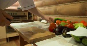 Mãos do ` s do cozinheiro chefe Homem na roupa branca que desbasta vegetais Pimento, tomate, pepino e verde frescos no fundo filme