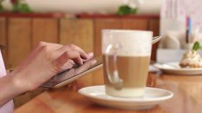 Mãos do ` s da menina com tabuleta e xícara de café no café vídeos de arquivo