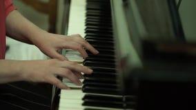 Mãos do ` s da menina no teclado do piano A menina joga o piano, fim acima do piano Mãos nas chaves brancas do piano filme