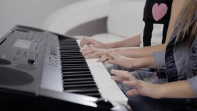 Mãos do ` s da menina no teclado do piano A menina joga o piano, fim acima do piano Mãos nas chaves brancas do piano video estoque