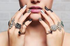 Mãos do ` s da mulher com anéis da joia Fotos de Stock Royalty Free