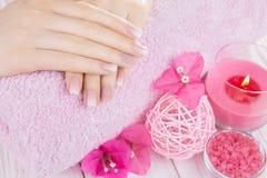 Mãos do ` s da mulher com tratamento de mãos francês imagem de stock