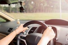 Mãos do ` s da mulher de um motorista no volante de um carro fotos de stock royalty free