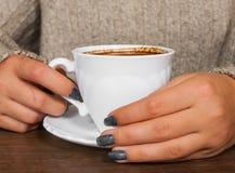 Mãos do ` s da mulher na camiseta que guarda a xícara de café Foto de Stock Royalty Free