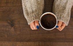 Mãos do ` s da mulher na camiseta que guarda a xícara de café Foto de Stock