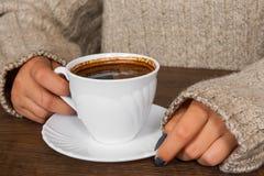 Mãos do ` s da mulher na camiseta que guarda a xícara de café Imagem de Stock Royalty Free
