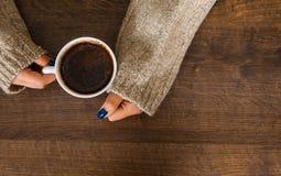 Mãos do ` s da mulher na camiseta que guarda a xícara de café Fotos de Stock Royalty Free