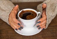 Mãos do ` s da mulher na camiseta que guarda a xícara de café Fotos de Stock