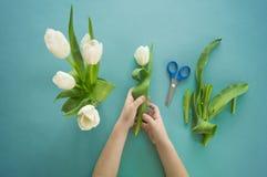 Mãos do ` s das crianças com um ramalhete da opinião superior das tulipas Fundo para um cartão do convite ou umas felicitações A  Imagens de Stock Royalty Free