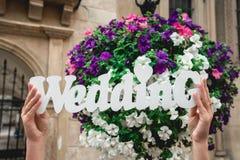Mãos do ` s das mulheres com a palavra do casamento no fundo das flores e das bolhas de sabão foto de stock