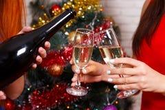Mãos do ` s das mulheres com uma garrafa e vidros completamente do champanhe, fim Fotos de Stock