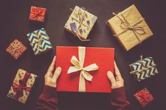 Mãos do ` s das mulheres que guardam a caixa de presente O presente encaixota o fundo Fotografia de Stock