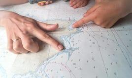 Mãos do ` s do adulto e das crianças no mapa imagens de stock royalty free