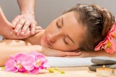 Mãos do ` s do massagista que fazem o ombro da massagem fotografia de stock