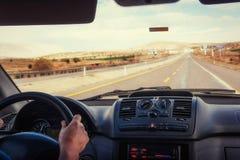 Mãos do ` s do motorista no volante de um carro fotos de stock royalty free