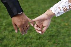 Mãos do ` s dos noivos com dedos juntados Imagens de Stock Royalty Free