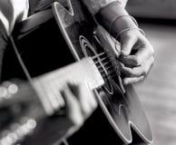 Mãos do ` s do homem do close up, dedos, arranhando a guitarra acústica com picareta imagem de stock royalty free