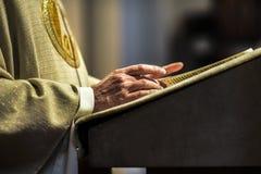Mãos do sacerdote católico que leem uma Bíblia fotografia de stock royalty free